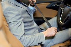 Feche acima da correia de segurança do assento da asseguração do homem no carro fotos de stock royalty free