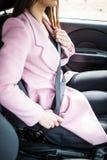 Feche acima da correia de segurança fêmea da asseguração no carro antes da movimentação imagens de stock royalty free