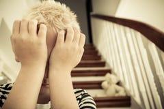 Feche acima da criança com mãos contra sua cara foto de stock royalty free