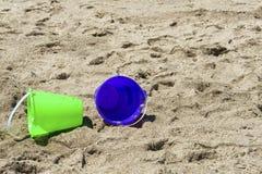 Feche acima da cubeta verde e roxa na praia imagens de stock