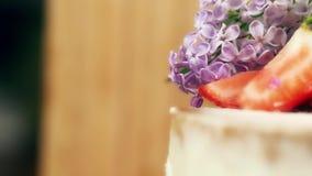 Feche acima da decoração no bolo feito a mão com bolinhos de amêndoa, as morangos cortadas e o tiro interior lento lilás das flor filme