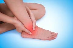 Feche acima da dor masculina de sofrimento no tornozelo no fundo azul fotos de stock
