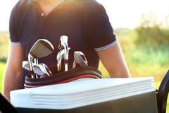 Feche acima da engrenagem do golfe profissional no campo de golfe no por do sol Foto de Stock
