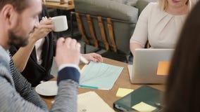 Feche acima da equipe criativa do negócio que senta-se em torno da tabela e discuta detalhes do projeto no escritório startup video estoque
