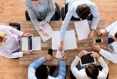 Feche acima da equipe do negócio com papéis e dispositivos Fotos de Stock