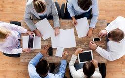Feche acima da equipe do negócio com papéis e dispositivos Imagem de Stock Royalty Free