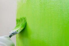 Feche acima da escova que pinta a cor verde na parede imagens de stock royalty free