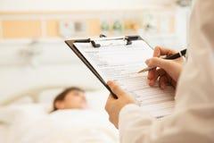 Feche acima da escrita do doutor em uma carta médica com o paciente que encontra-se em uma cama de hospital no fundo foto de stock