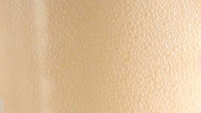 Feche acima da espuma da cerveja em um vidro filme