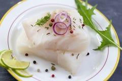 Feche acima da faixa de peixes crua fresca do bacalhau em uma placa com a salsa e o limão isolados no fundo cinzento da ardósia imagem de stock