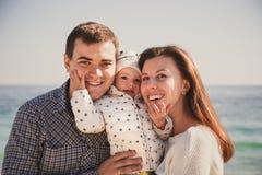 Feche acima da família loving feliz nova com a criança pequena no meio, tendo o divertimento na praia junto perto do oceano, esti Imagem de Stock Royalty Free