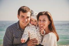 Feche acima da família loving feliz nova com a criança pequena no meio, tendo o divertimento na praia junto perto do oceano, esti Fotos de Stock
