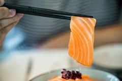 Feche acima da fatia salmon tomou por hashis os salmões cobriram pelos salmões frescos servidos com molho do wasabi e de soja Fotografia de Stock Royalty Free