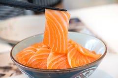 Feche acima da fatia salmon tomou por hashis os salmões cobriram pelos salmões frescos servidos com molho do wasabi e de soja Fotos de Stock Royalty Free