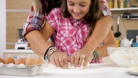 Feche acima da filha amassam a massa na cozinha video estoque