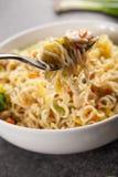 Feche acima da forquilha pronta para tomar um bocado do mein chinês do lo da galinha Imagens de Stock Royalty Free