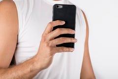 Feche acima da foto de um homem que guarda um telefone celular e que toma um auto Fotografia de Stock