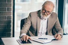 Feche acima da foto do homem de negócios superior cinzento-de cabelo considerável que trabalha com tabuleta imagens de stock royalty free