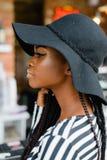 Feche acima da foto do portrate da menina consideravelmente americana atrativa Vista fêmea em algum lugar Modelo no chapéu negro foto de stock
