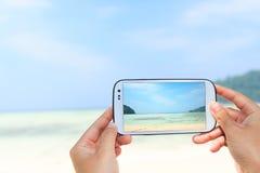 Feche acima da fotografia esperta da tomada do telefone do uso da mão a praia Imagens de Stock Royalty Free