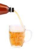 Feche acima da garrafa da cerveja que derrama em uma caneca. Fotos de Stock