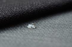 Feche acima da gota da água na matéria têxtil cinzenta do gunny Conceito para superfícies limpas, impermeáveis fáceis fotografia de stock