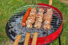 Feche acima da grade do assado com a carne e as salsichas que cozinham durante a SU Imagem de Stock