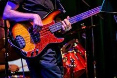 Feche acima da guitarra-baixo que está sendo jogada em um desempenho da fase fotografia de stock