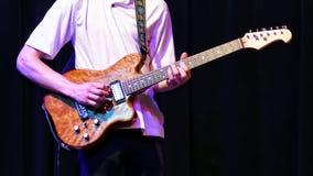 Feche acima da guitarra elétrica que está sendo jogada em um desempenho da fase fotografia de stock royalty free