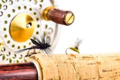 Feche acima da haste e do carretel de pesca com mosca no fundo branco Imagem de Stock Royalty Free