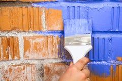 Feche acima da ideia da mão com a escova de pintura na cor azul Foto de Stock Royalty Free