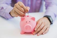 Feche acima da ideia da mão de um homem que coloca uma moeda no entalhe de um mealheiro Imagens de Stock Royalty Free