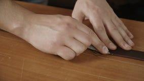 Feche acima da ideia das mãos do ` s do artesão que trabalham com uma parte de couro na tabela vídeos de arquivo