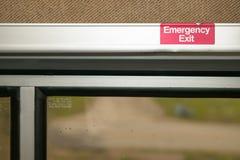 Feche acima da ideia de um sinal da saída de emergência para dentro Fotografia de Stock Royalty Free