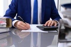 Feche acima da ideia do guarda-livros ou das mãos financeiras do inspetor que fazem o relatório, calculando ou verificando o equi imagem de stock
