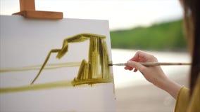 Feche acima da ideia do processo do desenho Imagem fêmea do óleo da pintura do artista com escova filme