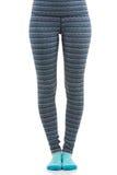 Feche acima da ideia dos pés da mulher do ajuste que vestem a calças listrada colorida dos esportes e peúgas azuis da vista diant Imagens de Stock
