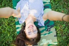 Feche acima da ideia superior de rir a mulher moreno nos monóculos que encontram-se na grama no parque e que fazem o selfie imagem de stock