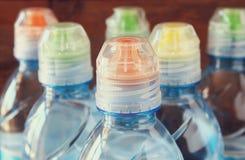 Feche acima da imagem de bottels da água sobre o fundo de madeira Fotografia de Stock Royalty Free