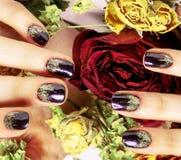 Feche acima da imagem de pregos do tratamento de mãos com a rosa seca do vermelho da flor, deh Fotografia de Stock Royalty Free