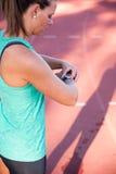 Feche acima da imagem de um atleta fêmea que ajusta seu moni da frequência cardíaca Foto de Stock Royalty Free