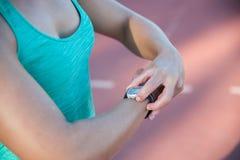 Feche acima da imagem de um atleta fêmea que ajusta seu moni da frequência cardíaca Fotos de Stock Royalty Free