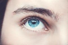 Feche acima da imagem do olho humano azul do olhar perspicaz foto de stock