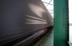 Feche acima da imagem do trem de mercadorias no movimento na ponte Imagens de Stock