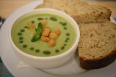 Feche acima da imagem da fotografia do alimento das fatias verdes cozinhadas quentes da sopa vegetal e do pão de mistura servidas Fotografia de Stock