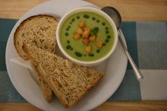 Feche acima da imagem da fotografia do alimento da sopa vegetal verde cozinhada quente com pão torrado e fatias do pão de mistura Foto de Stock Royalty Free