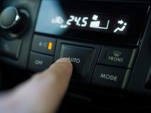 Feche acima da imprensa do dedo o botão para girar sobre a condição do ar no carro fotografia de stock