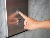 Feche acima da imprensa da mão do homem um botão ascendente do elevador dentro da construção fotos de stock royalty free