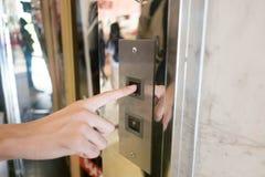 Feche acima da imprensa da mão do homem um botão ascendente do elevador dentro da construção para o assoalho de nível elevado sup imagens de stock royalty free