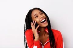 Feche acima da jovem mulher alegre com cabelo trançado que fala no telefone celular e no riso imagem de stock royalty free
